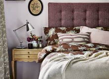 Pink bedroom with floral duvet cover and tall tweed headboard