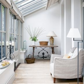 Informal Conservatory with White Walls and Wooden Furniture