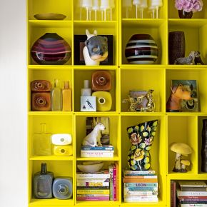 Bright yellow shelving unit with quirky ornaments