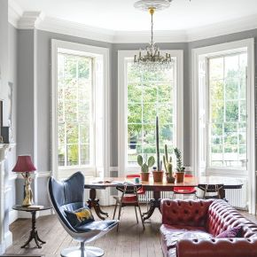 Bright Open Living Room With Stripped Wood Floor and Chandeliers