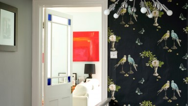 Hallway with bold bird print wallpaper and feature light