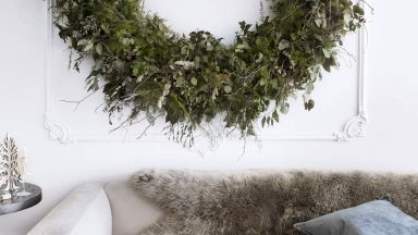 Cosy white living room with supersized Christmas wreath