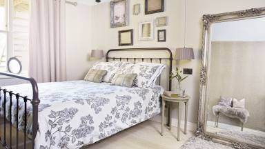 Traditional Bedroom with Iron Bedstead and Ornate Mirror