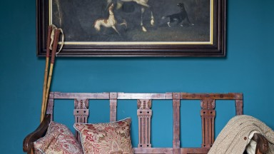 Traditional hallway with dark teal wall and bench