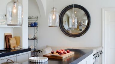 White kitchen with black worktops and glass pendant lights