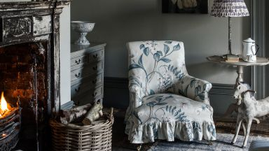 Grey Country Living Room with Floral Armchair and Rustic Fireplace