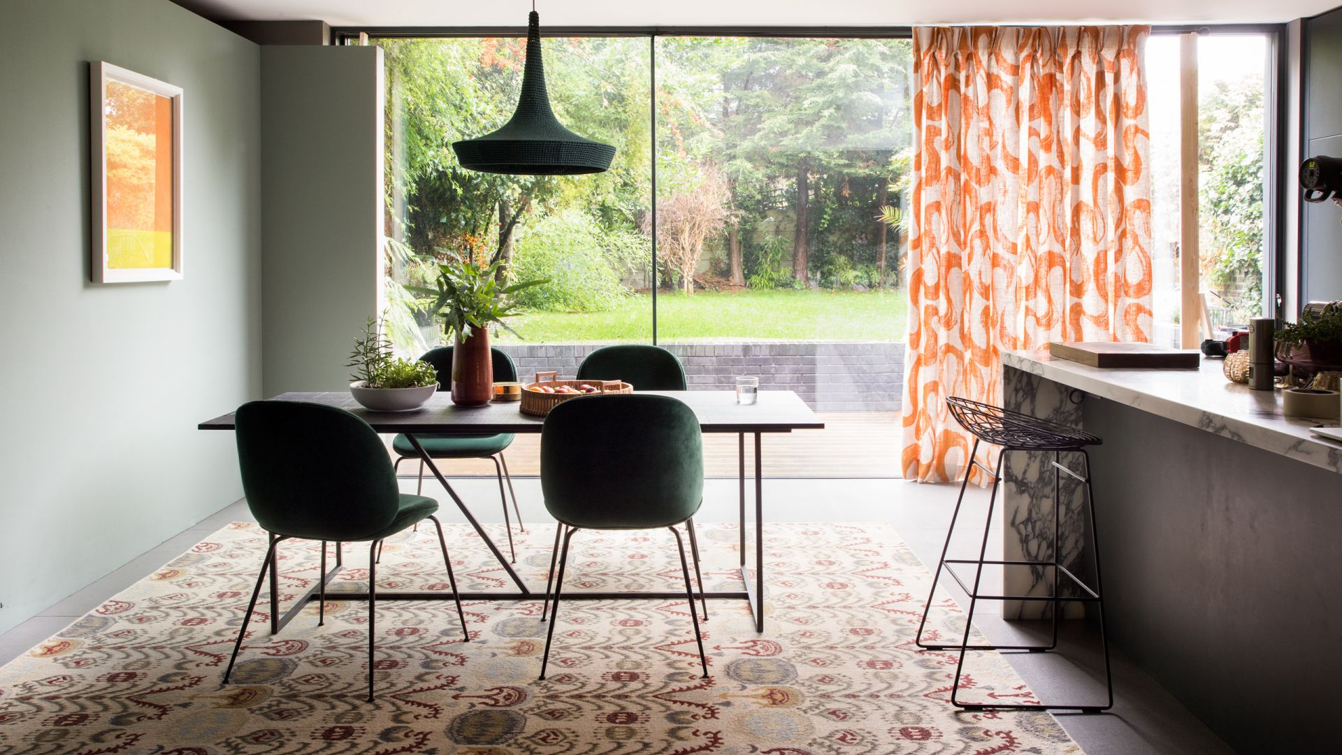 Chic Modern Dining Area With Statement Rug and Curtain