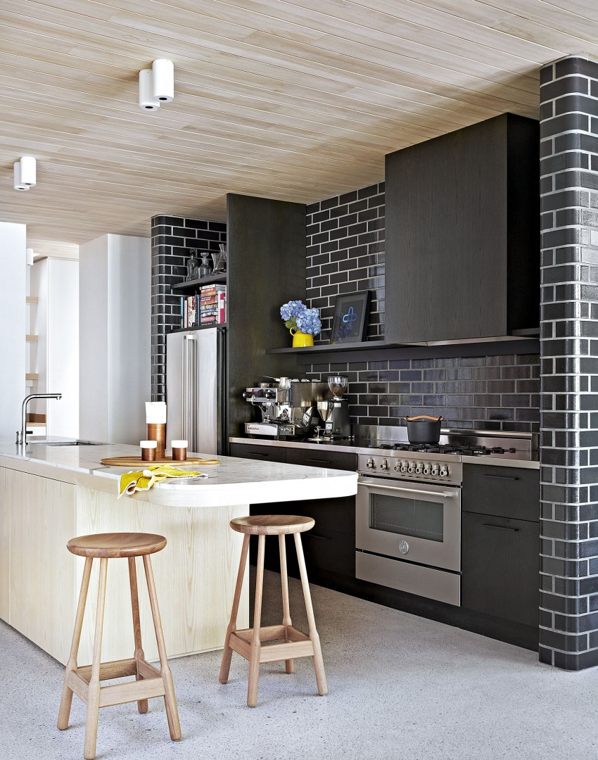 Modern kitchen with black tiled wall