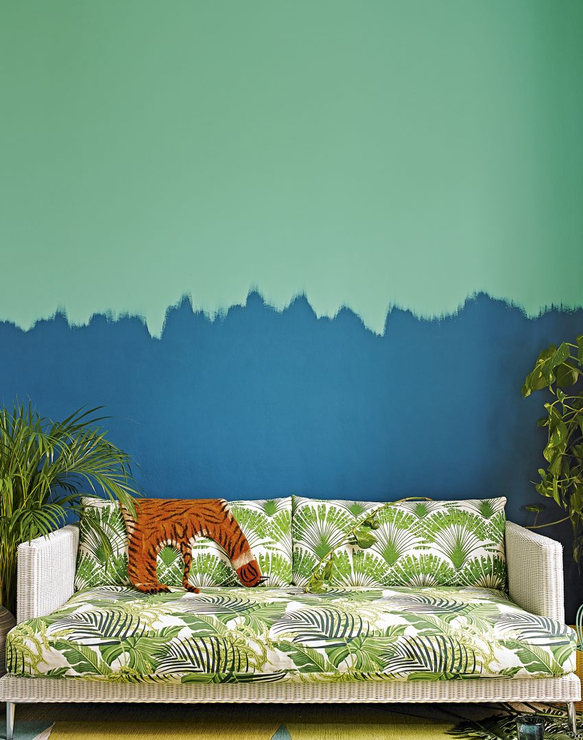 Modern tropical living room with vibrant palm-print sofa