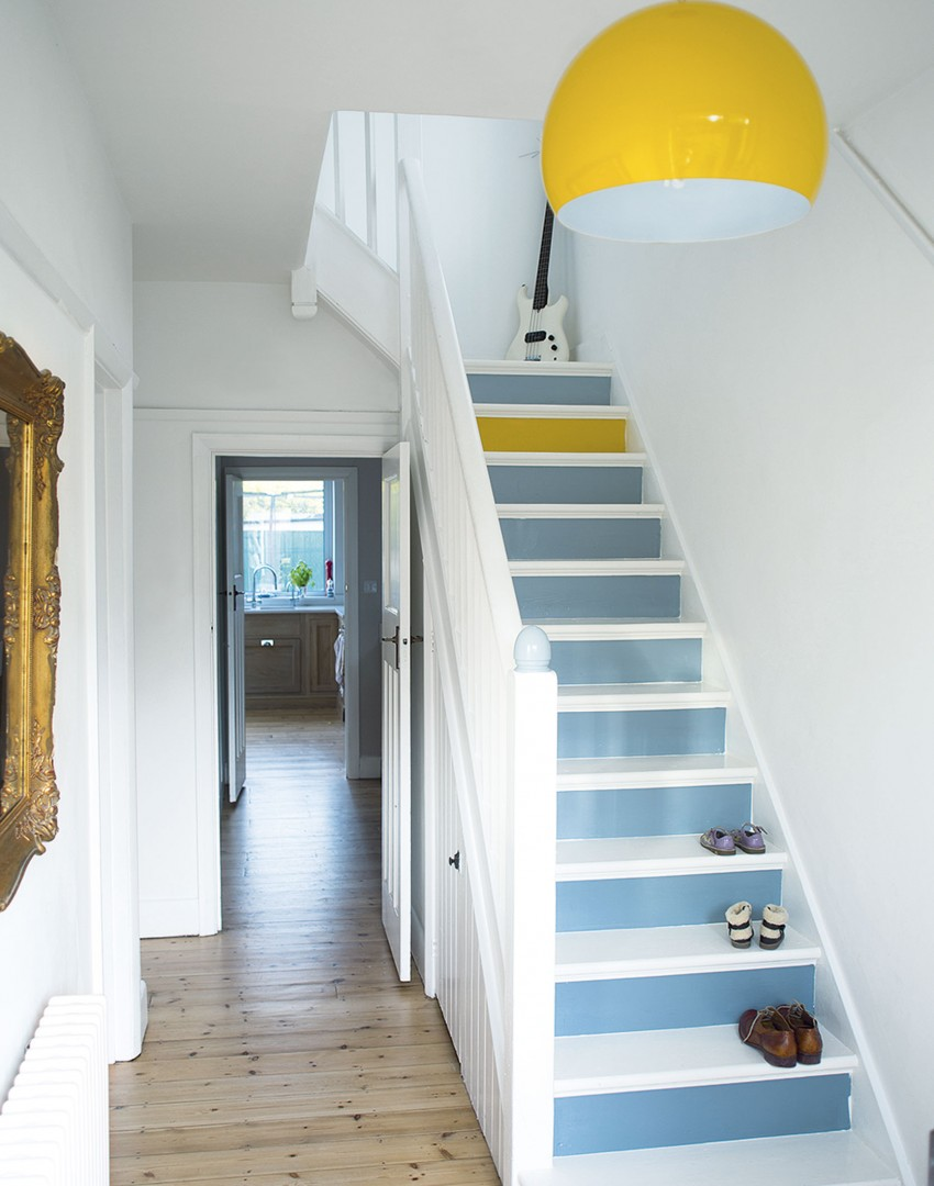 White hallway with painted stairs