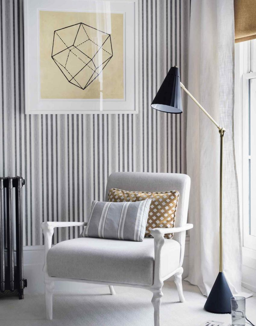 Pinstriped bedroom corner with geometric wall art